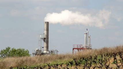 Smoking industrial chimney behind a field in front of sky