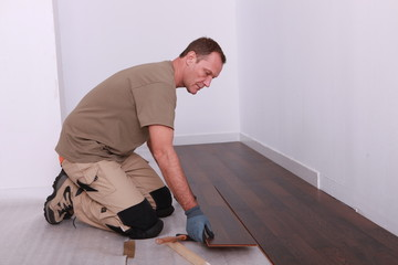 Man installing parquet flooring