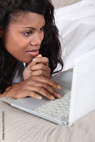 Black lady using laptop in bed