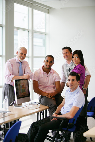 Group of colleagues gathered around computer