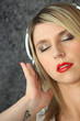 blonde woman with closed eyes listening to music