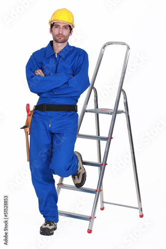 Laborer leaning on a ladder, studio shot