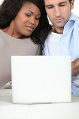 Mixed race couple with laptop