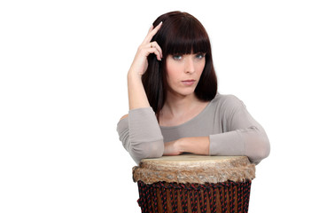 Pensive woman resting on a drum