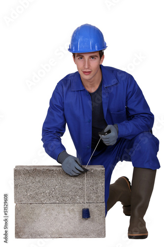 Bricklayer in blue overalls