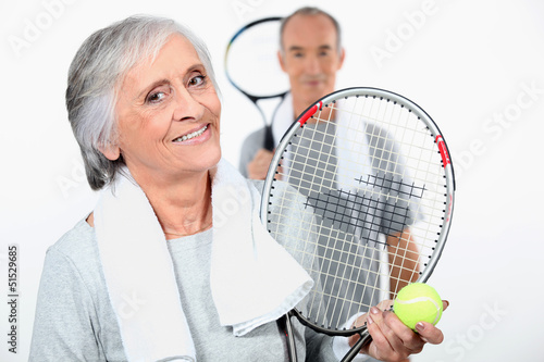 Elderly couple playing tennis