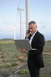 Businessman using his laptop and phone in the middle of nowhere