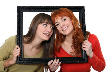 Two girls behind black frame