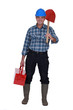 Tradesman carrying a spade and a toolbox