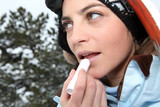 Female skier applying lip balm