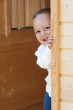 Child at playing  with wooden door