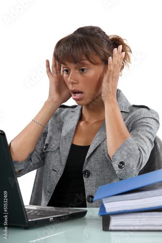 Alarmed woman looking at her laptop