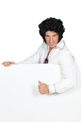 Man in an Elvis outfit and a board left blank for your image