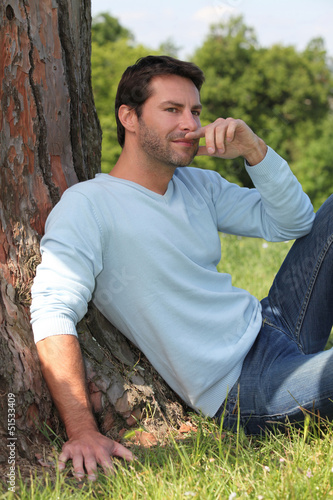 Man sitting against a tree.