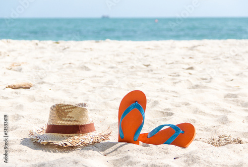 flip-flop and a woven hat on the beach. - 51533619