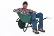 A man resting in a wheelbarrow.