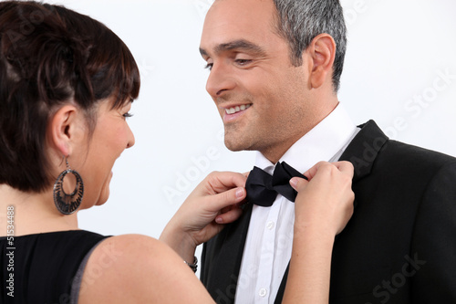 Wife helping husband with bow tie
