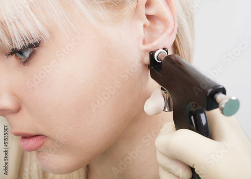 Woman having ear piercing process with special equipment