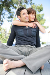Man sitting cross-legged and being hugged by his wife