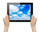 Woman hands holding tablet PC with sky on white background .