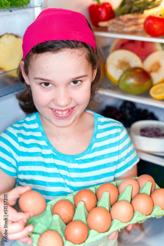 Mädchen mit Eiern vor offenen Kühlschrank