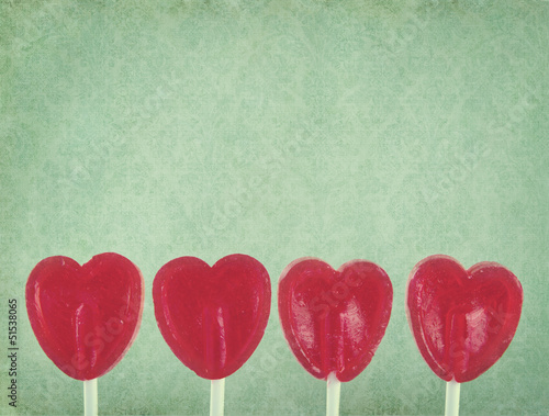 Row of red lollipop hearts on vintage background