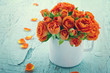 Vintage edited orange roses in a white cup