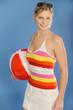 Junge attraktive Blondine mit einem Strandball