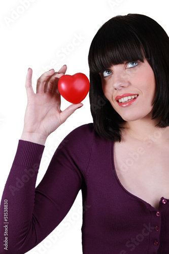 Young woman holding a small red heart