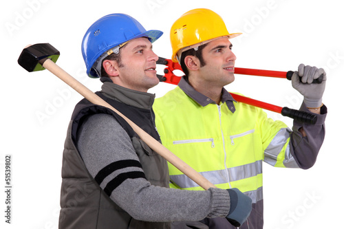 Two manual workers stood together looking into the distance