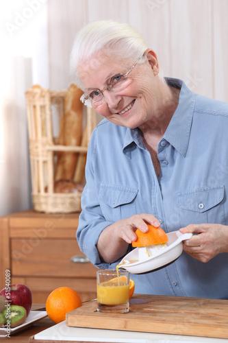 Elderly woman pouring freshly squeezed orange juice
