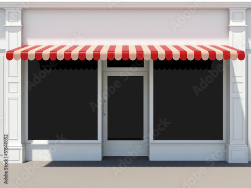 Shopfront in the sun - classic store front with red awnings