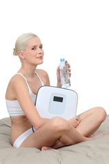Young woman in her underwear with scales and a bottle of water