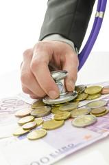 Detail of banker hand holding stethoscope over Euro money