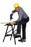 Man using a drill at a workbench poster