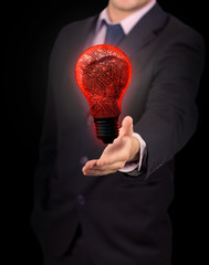 Businessman holding red light bulb