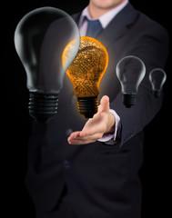 Businessman holding orange light bulb