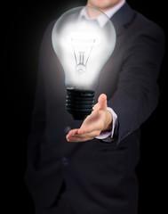 Businessman holding big light bulb lighting