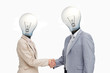 Business people with lightbulb heads greeting with a handshake