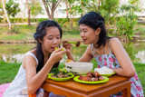 Asian Thai girls picnic together beside swamp.