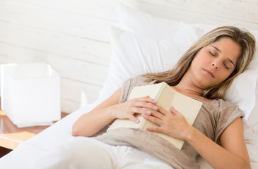 Tired woman reading a book