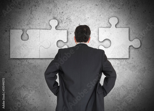 Businessman figuring out puzzle