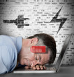 Businessman sleeping on laptop with energy and charging symbols