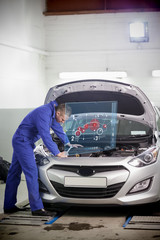 Man repairing car with open hood and small futuristic interface