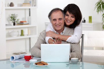 Couple smiling in front of their laptop