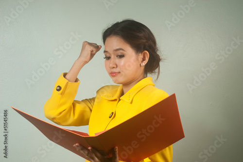 Pretty Asian businesswoman complacent reading a file.