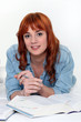 redhead girl lying in bed studying
