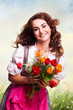 junge Frau im Dirndl mit einem Strauß Tulpen
