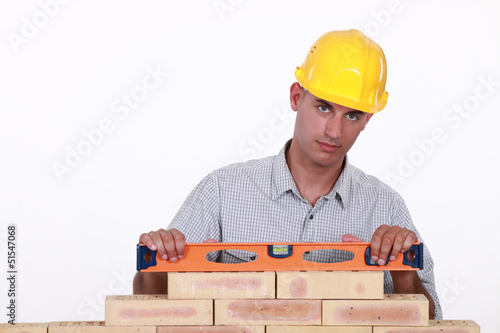 Bricklayer using a bubble level