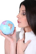 Woman blowing on a mini globe